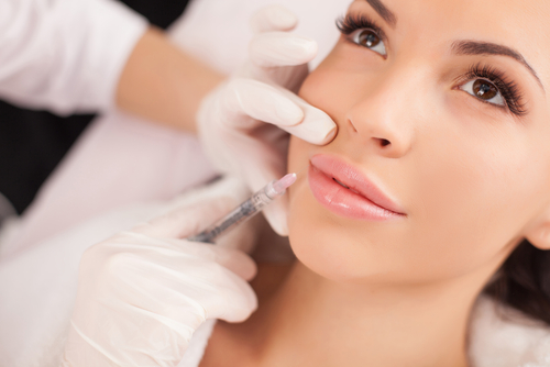 close up of hands of cosmetologist making dysport injection in female lips-img-blog